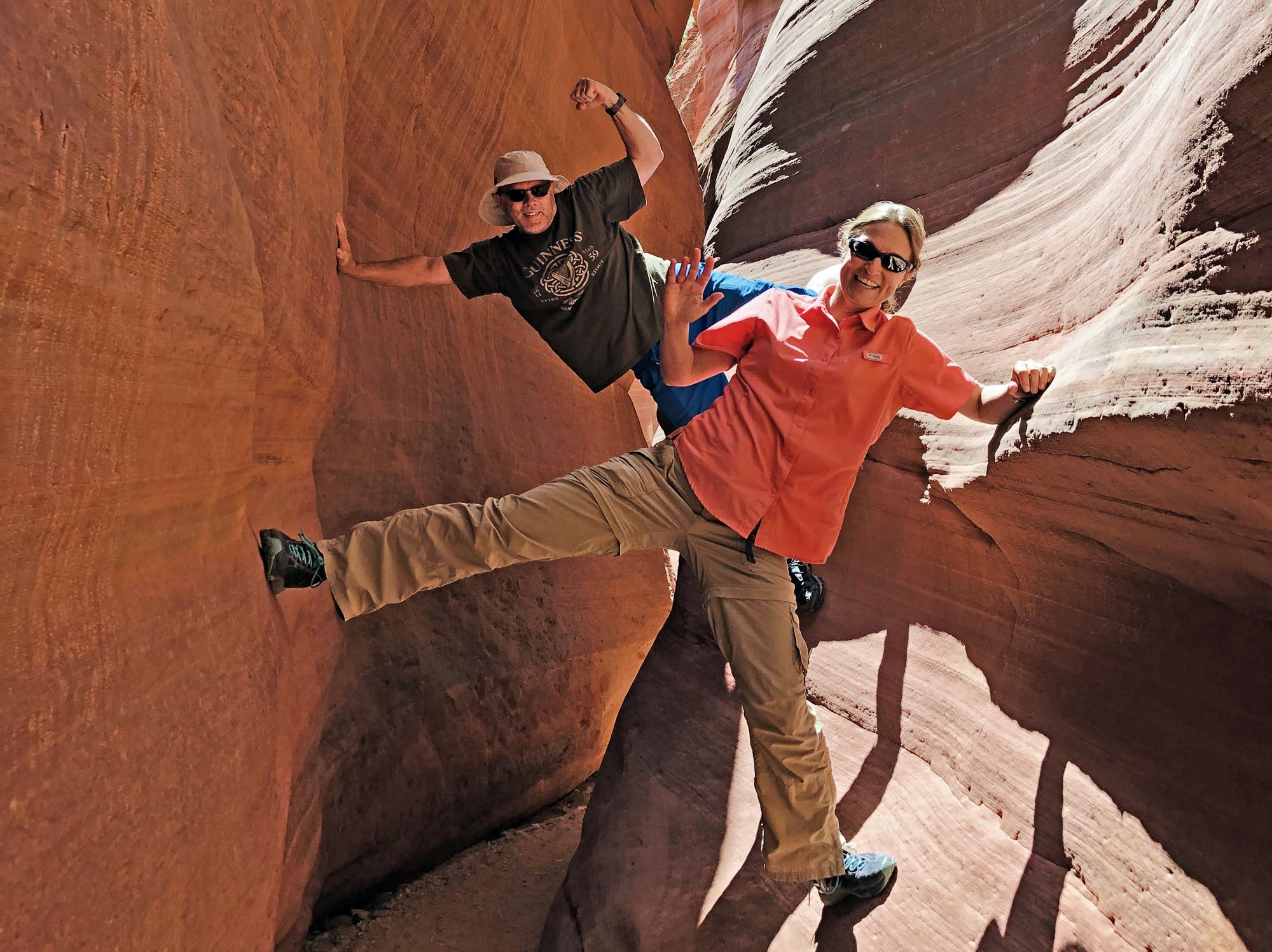 Tour guide poses with guest in slot canyon