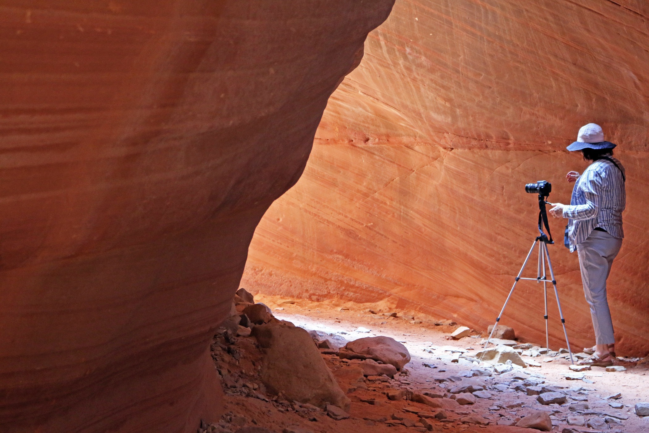 Woman with tripod in slot canyon